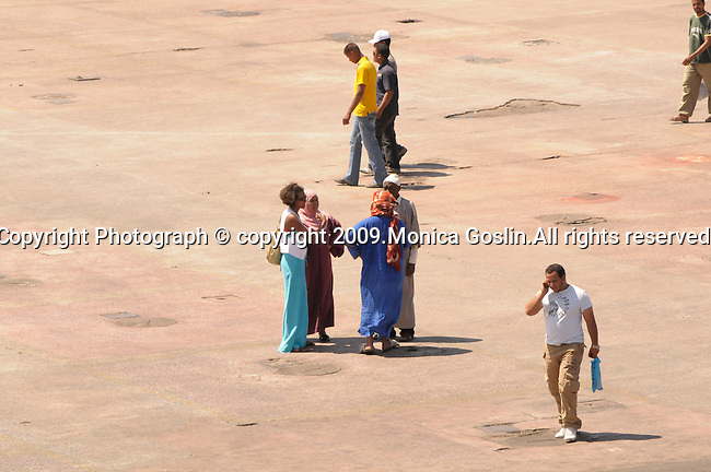 People in the sunny square, Place Djemaa El-Fna, in Marrakesh, Morocco.