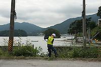 A Construction worker digging during reconstruction efforts following the 311 Tohoku Tsunami in Ofunato, Japan  © LAN