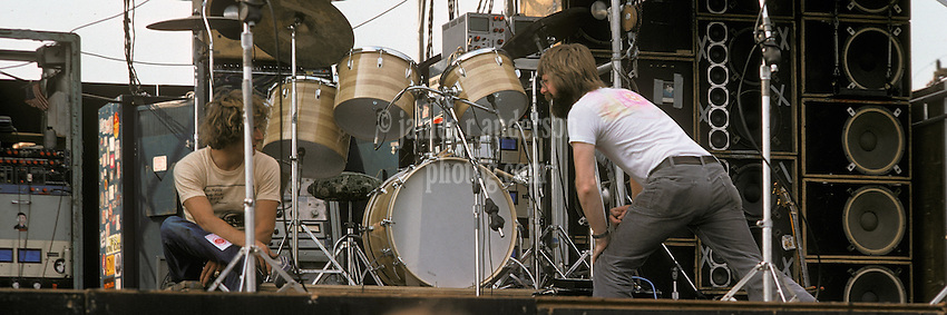 "Phil Lesh and Ram Rod in conversation on stage before the Grateful Dead Play Live at Dillon Stadium, Hartford, CT 31 July 1974. Featuring the Wall of Sound. Summer weekday show, one of the longest ever played by The Dead. Deadheads hanging out, Crew setting up. Cropped for panoramic, example: 10x30"", prints."