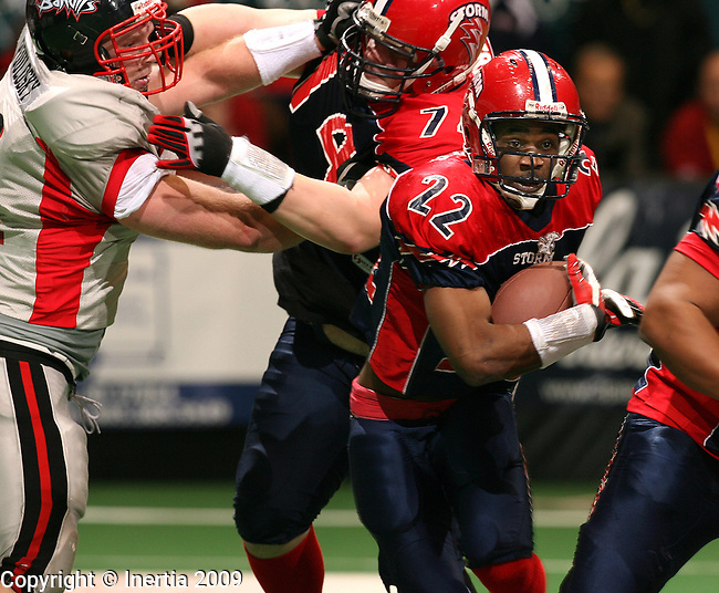 SIOUX FALLS, SD - APRIL 18:  Marques Smith #22 of the Sioux Falls Storm breaks through the line past the block of teammate Zac Tubbs #74 on Andy Poulosky #51 of the Sioux City Bandits in the second quarter of their game Saturday night at the Sioux Falls Arena.(Photo by Dave Eggen/Inertia)