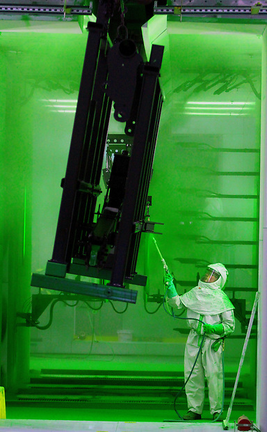 Painter Dale Anderson applies the familiar John Deere green to farm implement parts at John Deere Des Moines Works in Ankeny.