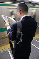 Commuters wait on the platform. This man has rucksack on back to front. Tokyo has one of the most extensive and efficient transport networks in the world - but also one of the most crowded. Rail companies calculate crowding by percent of standard capacity (ie when all the seats and standing spaces are occupied). Some trains reach 220%+.