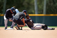 GCL Yankees East Yeison Corredera (87) gets looked at by trainer Anthony Moon and manager Raul Dominguez after a play at second base during a game against the GCL Pirates on August 15, 2016 at the Pirate City in Bradenton, Florida.  GCL Pirates defeated GCL Yankees East 5-2.  (Mike Janes/Four Seam Images)