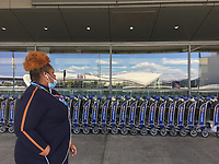 NEW YORK, NY - MAY 12: A woman wearing a face mask crosses the front of the baggage carts at JetBlue Terminal 5 of the John F. Kennedy International Airport on May 12, 2020 in New York, NY. Although some airlines have routes during this pandemic from the John F. Kennedy International Airport, others like Avianca Holdings declare bankruptcy due to the COVID-19 crisis, the bankruptcy declaration of the Colombian airline was stimulated by COVID travel restrictions. -19, which have reduced the company's revenue by more than 80% (Photo by Pablo Monsalve / VIEWpress via Getty Images)