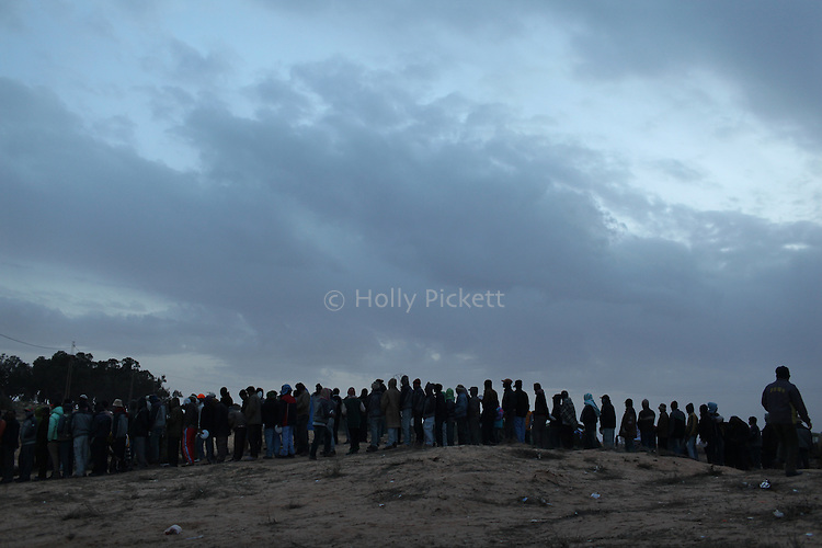 Refugees wait in line for supper at a camp near the Tunisian side of the Ras Jidir border crossing with Libya, March 3, 2011. More than half of the 180,000 people estimated to have fled Libya have crossed into Tunisia. Thousands of Egyptian, Bangladeshi and Sri Lankan migrant workers are stuck at the border as aid organizations and governments struggle to get them home via an airlift operation. Meanwhile, many refugees have been sleeping outside on the ground, in some cases for four or more days.