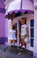 Small boy and girl outside a pink toy house in Disney World, Florida, USA