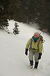 Woman hiker (MR) dressed for the cold and wind, in subalpine forest, winter, Rocky Mountain National Park; snowing, February 2008, Colorado, USA, Rocky Mountains