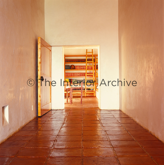 A rustic ladder against a wall of bookshelves is at the end of this corridor with its shiny plaster walls and terracotta floor tiles