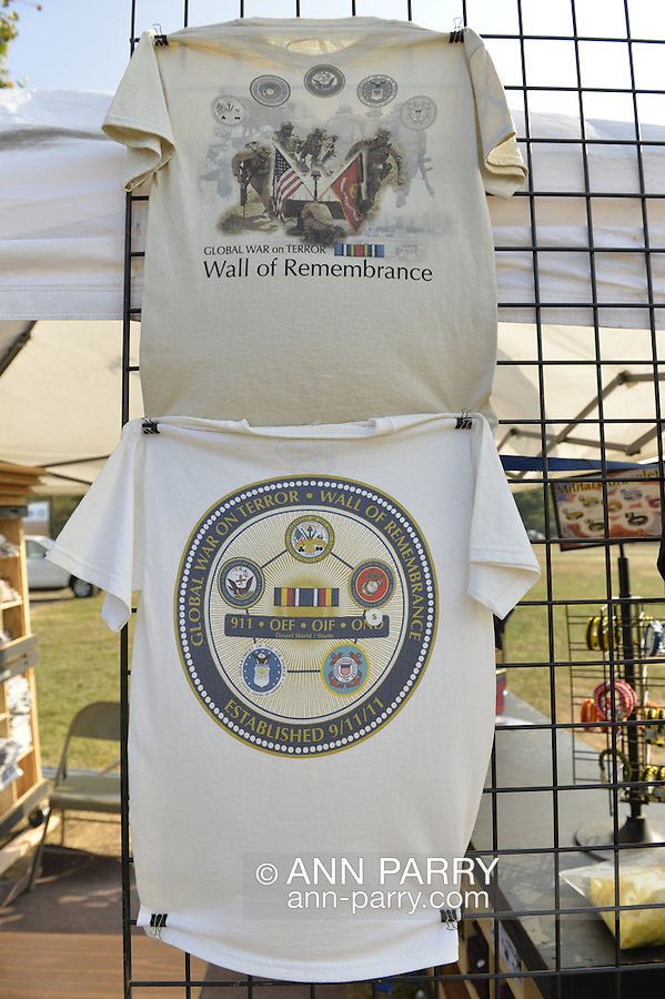 "East Meadow, New York, U.S. 11th September 2013. T-shirts for sale are on disaply at the booth by the Global War on Terror ""Wall of Remembrance"" a traveling memorial on display in New York for the first time, at Eisenhower Park on the 12th Anniversary of the terrorist attacks of 9/11. The unique 94 feet long by 6 feet high wall has, on one side, almost 11,000 names of those lost on September 11, 2001, along with heroes and veterans who lost their lives defending freedom of Americans over past 30 years. On the wall's other side is a timeline, with photos, covering 1983 to present day."