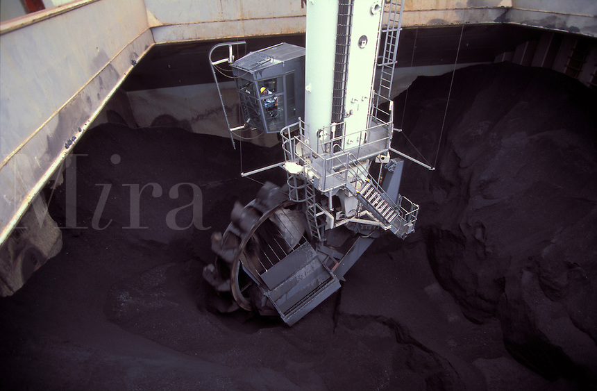 Continuous coal unloader working in the hold of a ship.