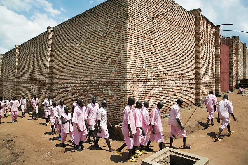Rwanda. Southern province. District of Muhanga. Central jail of Gitarama. A group of black teenager boys, wearing the pink prisoner's clothes, walk outside of the prison. They are returning to the minors block. Bricks wall. Minors in detention. Detention pending trial and after trial, when sentenced to prison. The non-governmental organization (NGO) Fondation DiDé - Dignité en détention runs the Encademi (Encadrement des mineurs) program. Prison centrale de Gitarama. Quartier des mineurs.  © 2007 Didier Ruef