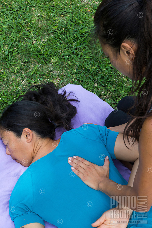 Massage therapist and Pranassage® practitioner Miki Sato works on a client at an outdoor location on O'ahu.
