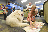 NWA Democrat-Gazette/FLIP PUTTHOFF <br /> FURRY READING PAL<br /> Rosemary Jonasson, 4, shows a picture book on Saturday July 6 2019 to Obi, a certified therapy dog, at the Rogers Public Library. Larry Gramling (second from right) of Centerton brought the great pyrenees dog to the library for children to pet and read books to Obi. Gramling and Obi make regular appearances at libraries, shelters and other locales including Northwest Arkansas Regional Airport. Obi lets passengers stroke his soft fur and helps soothe passengers who may be stressed.