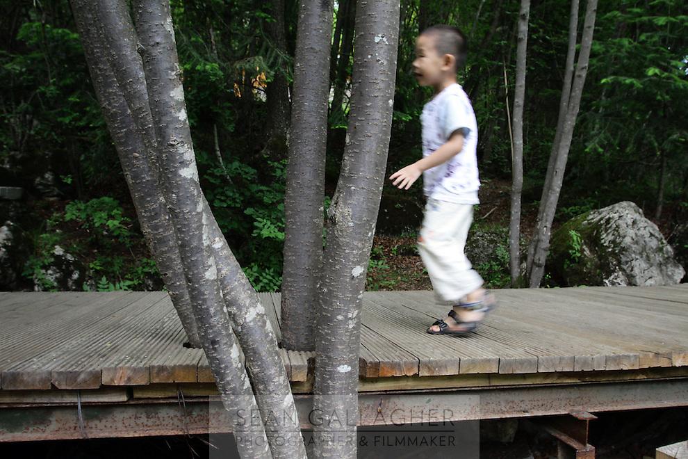 A young boy walk across a boardwalk in the Jiuzhaigou National Park. Sichuan Province. China.