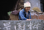 woman farmer (senior) with traditional head dress carrying basket stands behind wall; rural China near Wanxian; agriculture; 042103