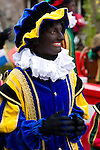 A female black pete, the helpers of Sinterklass, rides a boat through the canals of Utrecht to welcome Sinterklass to the dutch city, the Netherlands.