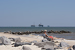Beach goer and gas rigs in the Gulf of Mexico off Fort Gaines