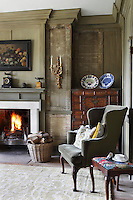 A fire blazes in the fireplace of the living room which retains its exposed original panelling. The cabinet in the corner is from Korea
