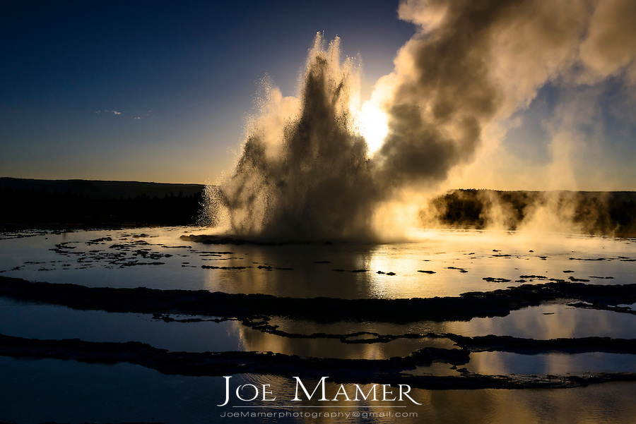 Great Fountain Geyser erupting at sunset in Yellowstone National Park.
