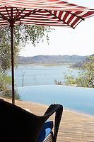 A view overlooking an infinity pool and lake beyond from a terrace of the Singita Pamushana Lodge, Malilongwe Trust, Zimbabwe