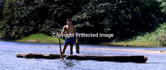 A native boy holds an iguana kill during a hunt for game along a remote stretch of the Macal River in western Belize.In front of him is a hand-hewed dugout canoe that the locals, who are direct descendents of the Mayans, use to traverse the winding river along the Guatemalan border.Iguanas are used as a food source for the natives. <br />