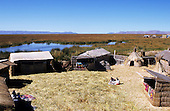Lake Titicaca, Peru. Typical houses made of reeds on the floating island of Uros with women in traditional dress.