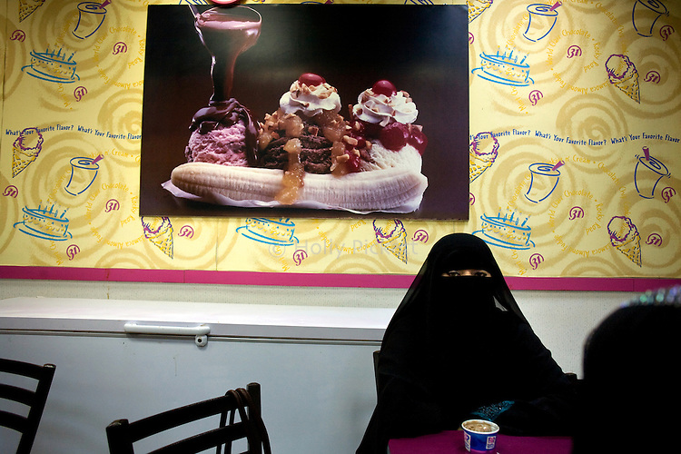 A woman sits in a Baskin Robbins ice cream shop in Aden, Yemen, Dec. 2, 2009. Although Aden is considered more liberal than other parts of Yemen, women still often opt for the niqab to cover their faces in public. Lawlessness, growing poverty, a water crisis, a raging conflict with Houthi rebels in Yemen's north and clashes with separatists in the South continue to destabilize the Arabian Peninsula's poorest state.
