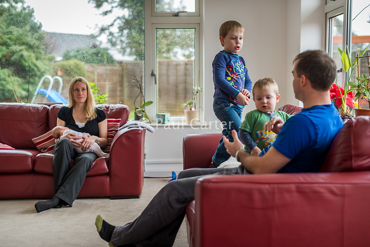 A woman sitting on her living room sofa and breastfeeding her 2 month old baby daughter while her two older boys play with their father on another sofa.<br /> <br /> Hampshire, England, UK<br /> 10/02/2013
