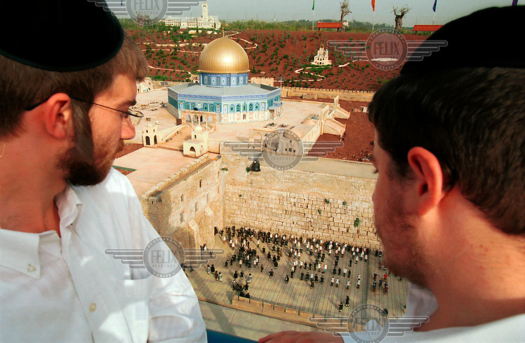 Ultra-Orthodox Jews look at a model of Jerusalem's Temple Mount compound, in the Mini Israel tourist attaction.