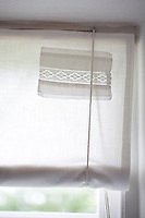 Homemade blinds made from old sheets and decorated with pieces of lace hang in the kitchen windows