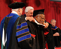 NWA Democrat-Gazette/ANDY SHUPE<br /> Judge L. Clifford Davis (right) smiles Saturday, May 13, 2017, as Ben Hyneman (center), chair of the Board of Trustees of the University of Arkansas System, awards Davis with an honorary degree while Joseph Steinmetz, chancellor, looks on during commencement exercises in Bud Walton Arena in Fayetteville. Visit nwadg.com/photos to see more photographs from the ceremony.