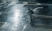 An unprepared bicyclist in a torrential summer rain storm in the Chelsea neighborhood of New York on Tuesday, July 7, 2015.  (© Richard B. Levine)