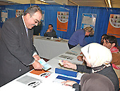 Doctor Mahdi S. Abdullah, M.D., of Mount Vernon, New York presents his passport and identification card to election officials as he votes in the Iraqi election in New Carollton, Maryland on January 28, 2005.  Doctor Abdullah, a Baghdad-born internist, fled Iraq in 1993 after several of his relatives were killed by Saddam Hussein's regime.  He expressed joy at voting in the first free Iraqi election during his lifetime..Credit: Ron Sachs , CNP..(RESTRICTION: NO New York or New Jersey Newspapers or newspapers within a 75 mile radius of New York City)
