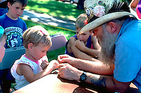 Volunteer age 55 teaching fly tying to 5 year old angler.  Minneapolis  Minnesota USA