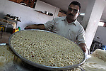 A Palestinian vendor prepares a traditional sweets at his shop in Gaza City on Sept 7,2010, as Muslims the world over prepare to celebrate Eid al-Fitr, a three day holiday marking the end of the religious month of Ramadan in which believers abstain from food and water during daylight hours . Photo by Mohammed Asad