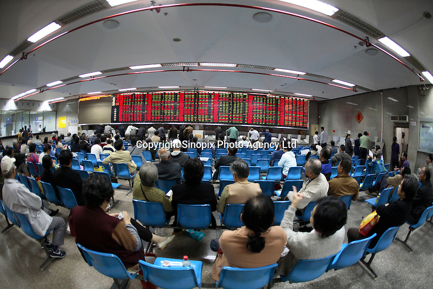Investors watch the stock trading board at a securities exchange in Shanghai, China..29 Oct 2007