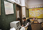 Oakland CA Kindergarten teacher working with students in classroom where class rules are on display