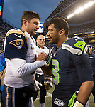 Seattle Seahawks quarterback Russell Wilson (3) greets St. Louis Rams quarterback Shaun Hill at the center of the CenturyLink Field in Seattle, Washington on December 28, 2014.  The Seahawks officially wrapped up the No. 1 seed in the NFC playoffs shortly after beating the Rams, 20-6. Despite the Cowboys and Packers also winning to finish 12-4, the Seahawks (12-4) won the multi-team tiebreaker and earned home-field advantage throughout the playoffs for the second consecutive season.  ©2014. Jim Bryant Photo. All Rights Reserved.