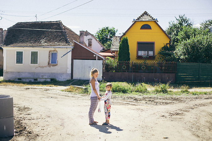 Die Volontaerin Marie Litauer wartet mit einem ein Kind aus dem Tageszentrum auf andere Kinder auf der Strasse waehrend des Nachhausebringens.  Europa, Rumaenien, Rusciori den 28. Juli 2015