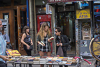 """Shoppers browse books along Bedford Avenue during """"Williamsburg Walks: Rethink Your Public Space"""" in the trendy hipster Williamsburg neighborhood of Brooklyn in New York on Saturday, June 8, 2013. The Dept. of Transportation closes several blocks in various neighborhoods for street activity where tables and chairs (and grass lawns) are set out and merchants vend their wares on the streets. © Richard B. Levine)"""