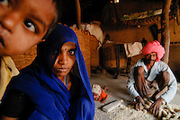 Indien Madhya Pradesh , Adivasi Familie vom Stamm der Bhil in ihrer Huette im Narmada Tal , Einbringen der Maisernte / INDIA Madhya Pradesh , tribal family of Bhil tribe in their hut in the Narmada valley, maize