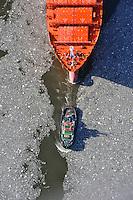 Hamburger Hafenschlepper zieht ein Schiff der Reederei Hamburg Sued: EUROPA, DEUTSCHLAND, HAMBURG, (EUROPE, GERMANY), 20.02.2012  Schlepper, auch Schleppschiffe genannt, (engl. tugboat oder tug) sind Schiffe mit leistungsstarker Antriebsanlage, die zum Ziehen und Schieben anderer Schiffe oder großer schwimmfaehiger Objekte eingesetzt werden. Meist werden zum Ziehen Schlepptrossen verwendet, die am Schlepper an Haken eingehaengt oder an Seilwinden aufgerollt sind. In Deutschland gibt es zusammen mit den Schubschiffen 450 Stueck