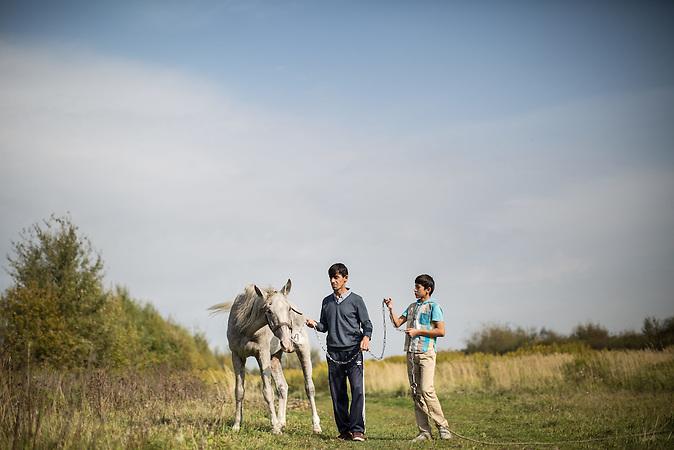Die Familie Musafirov lebt und arbeitet auf dem Bauernhof einer russischen Familie. / Tajik migrant worker Said Musafirov and his son Muhammed walk with a horse named as Russian poet Puskin in the village of Dubtsy outside Moscow