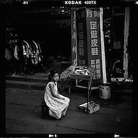 A Chinese girl sits outside a shop at a small traditional street in Suzhou, Jiangsu province, China, August 2012. (Mamiya 6, 75mm, Kodak TRI-X film)
