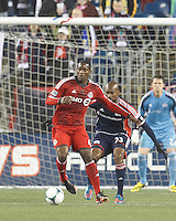 Toronto FC defender Doneil Henry (4) controls the ball as New England Revolution defender Jose Goncalves (23) defends. In a Major League Soccer (MLS) match, the New England Revolution (blue) defeated Toronto FC (red), 2-0, at Gillette Stadium on May 25, 2013.
