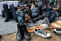 Pictured: Migrant men rest on the ground Friday 26 February 2016<br /> Re: Hundreds of refugees have temporarily camped at Victoria Square in central Athens, Greece.