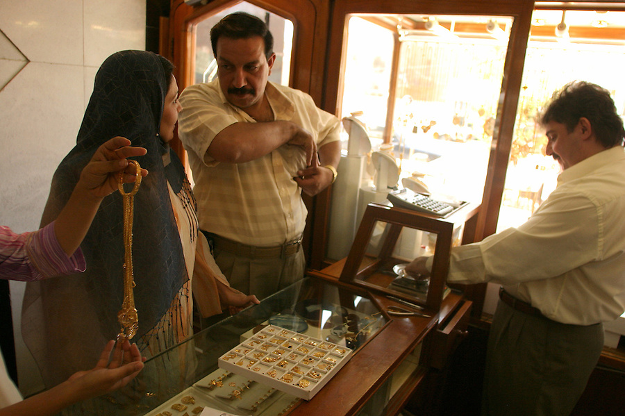 Ihsan al-Sabti behind the counter of his Baghdad gold jewelry shop displays his wares for customer Ibrahim Jaafar and his wife Zainab Jasim. The couple have come to his shop to buy presents for a business associate's birthday. Mr. al-Sabti has seen his sales double since the end of the war.