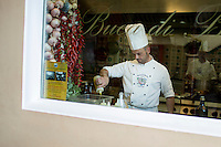 A chief works near a window at Buca di Bacco Restaurant on Sunday, Sept. 20, 2015, in Positano, Italy. (Photo by James Brosher)
