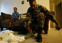 As his son Rickey Jr., 5,  quietly watches, Sgt. Rickey Moore laces his boots the morning of his deplyment Tuesday March 18, 2003, before the family leaves their Port Orange home for the National Guard Armory ion Daytona Beach.(Kelly Jordan)..**FOR DEPLOYMENT GALLERY**