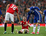 Michael Carrick of Manchester United is helped up by \mu236\ and Eden Hazard of Chelsea during the English Premier League match at Old Trafford Stadium, Manchester. Picture date: April 16th 2017. Pic credit should read: Simon Bellis/Sportimage